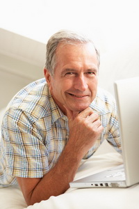 Senior Man Using Laptop Relaxing Sitting On Sofa