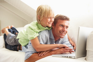 Father And Son Using Laptop Sitting On Sofa