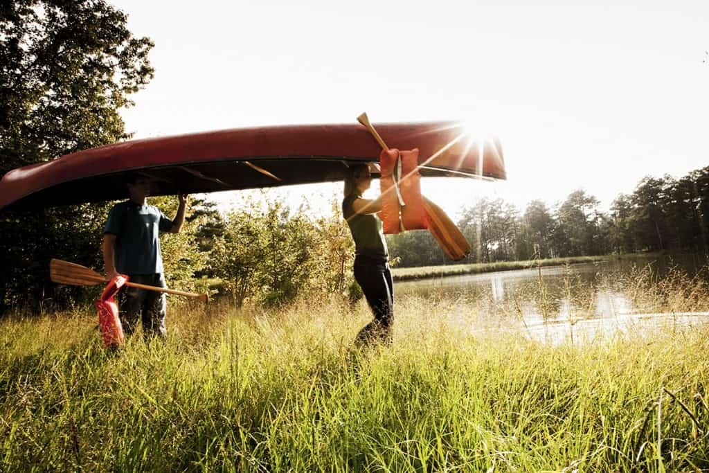 Young Couple Carry a Canoe (© Steve Cole)
